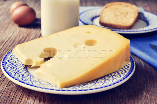 Stock photo: cheese, milk, eggs and bread on a rustic wooden table, with a fi