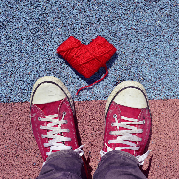 Stock photo: man in sneakers and heart-shaped coil of yarn on the asphalt