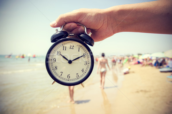 young man with an alarm clock on the beach Stock photo © nito