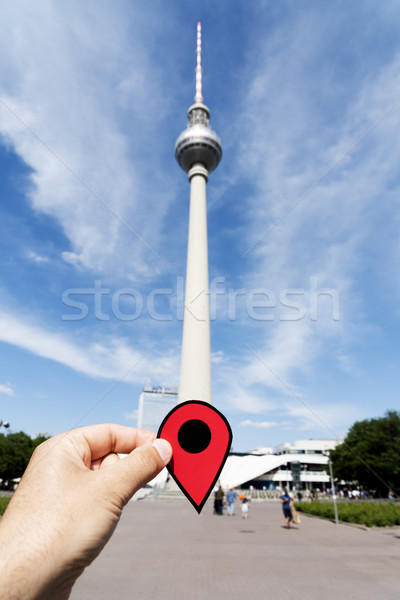 man with red marker at television tower of Berlin