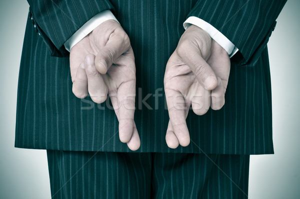 man wearing a suit crossing his fingers in his back Stock photo © nito