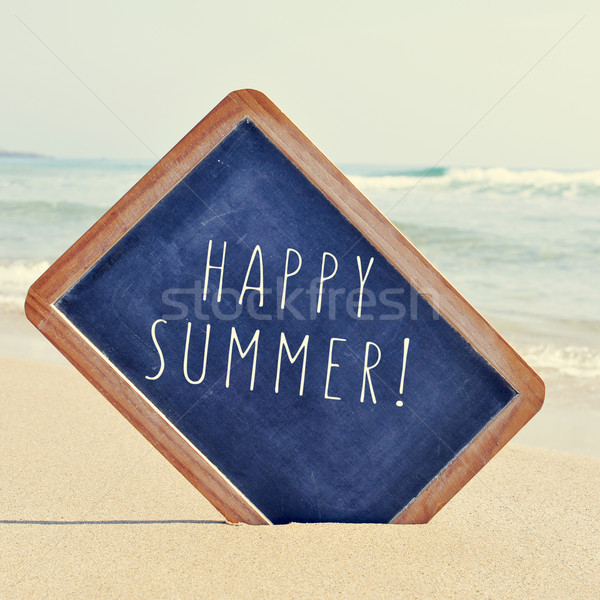 text happy summer in a chalkboard on the sand of a beach, with a Stock photo © nito