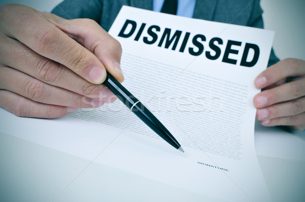 Stock photo: businessman shows a document with the text dismissed