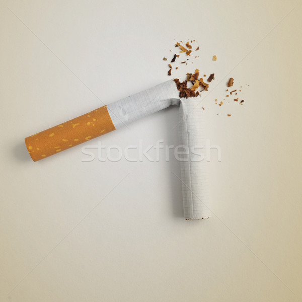 a broken cigarette on a beige background Stock photo © nito