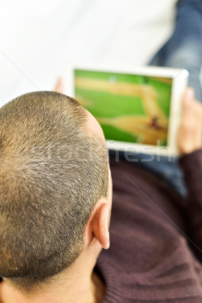 young man watching a baseball game in his tablet Stock photo © nito