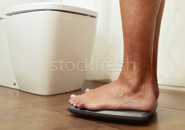 young man standing on a scale Stock photo © nito