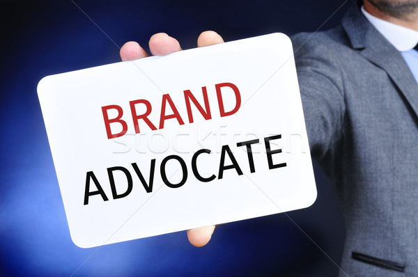businessman shows a signboard with the text brand advocate Stock photo © nito