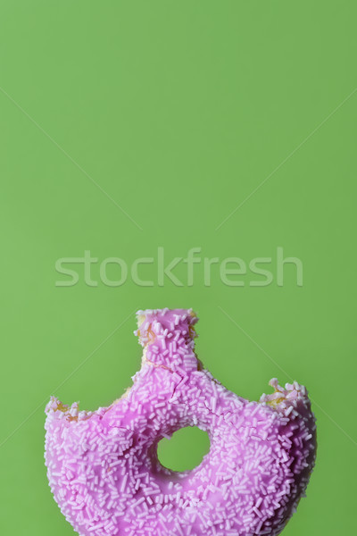nibbled pink donut on a green background Stock photo © nito