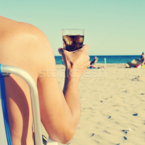 young man hanging out on the beach with a cola drink, filtered Stock photo © nito
