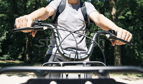 man riding a bike by a public park