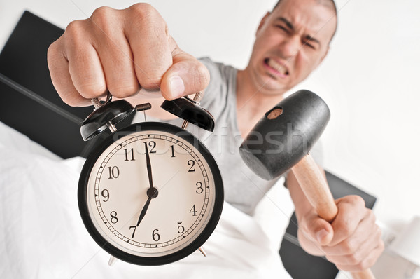 young man in bed about to hammer his alarm clock Stock photo © nito