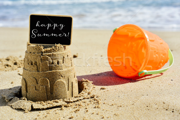 text happy summer in a signboard topping a sandcastle Stock photo © nito