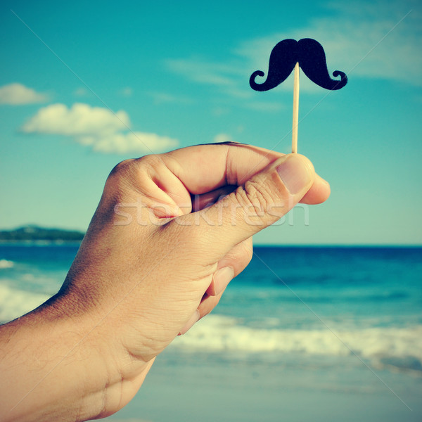 man hand with a fake moustache on the beach, with a filter effec Stock photo © nito