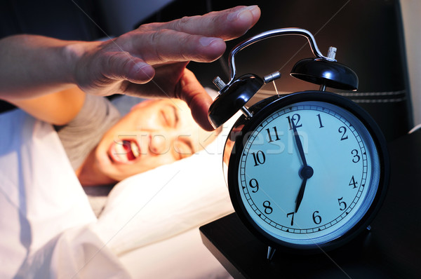 young man in bed stopping the alarm clock Stock photo © nito