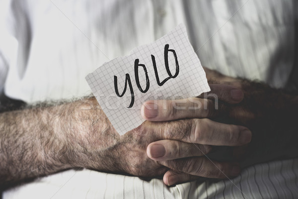 old man with a note with the word yolo Stock photo © nito