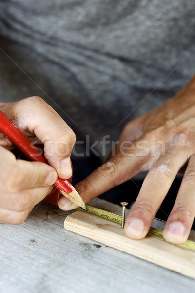 young man making a mark in a wood strip Stock photo © nito