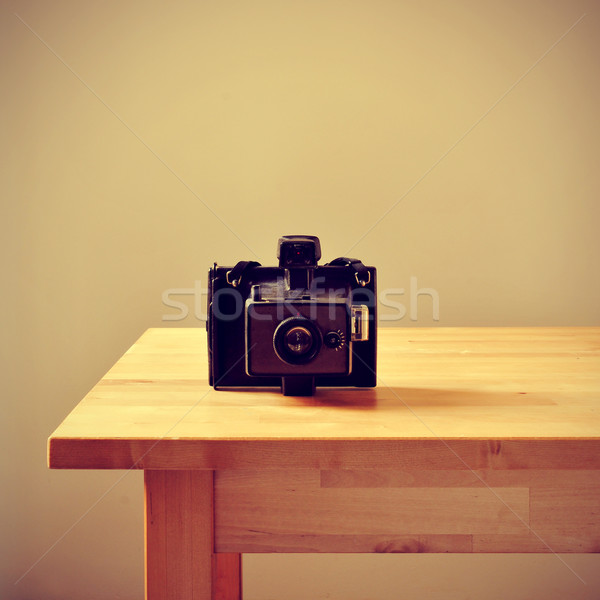 Stock photo: old instant camera on a table, with a retro effect