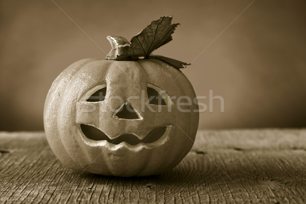 carved pumpkin on a wooden surface, in sepia toning Stock photo © nito