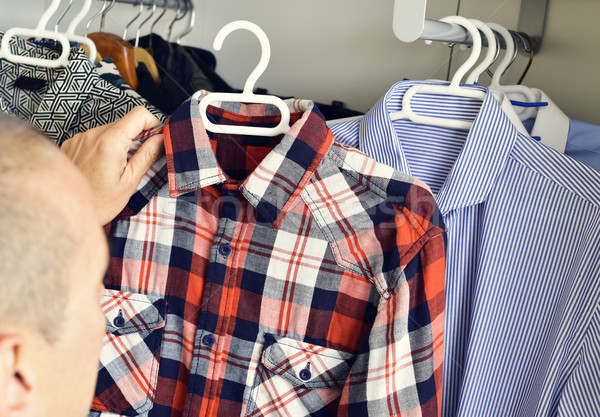 young man picking a shirt from the closet Stock photo © nito