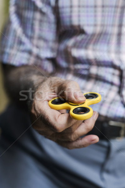 old man playing with a fidget spinner Stock photo © nito