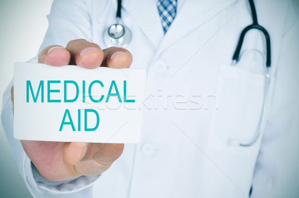doctor with a signboard with the text medical aid Stock photo © nito