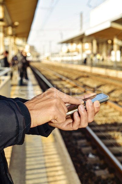 young man using a smartphone in a train station Stock photo © nito