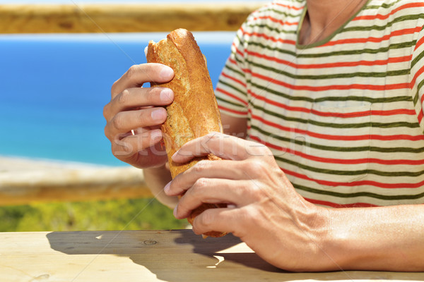 young man eating a sandwich outdoors Stock photo © nito