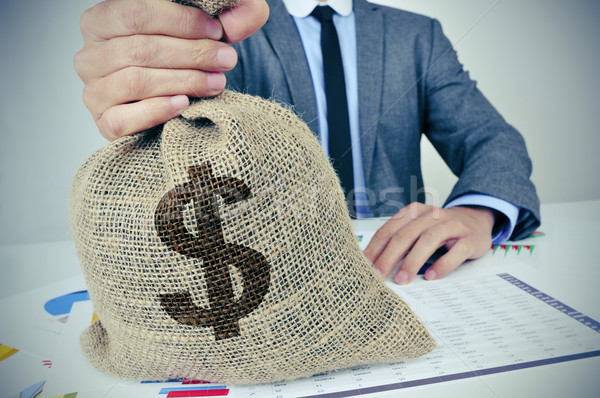 young man in suit with a burlap money bag with the US dollar sig Stock photo © nito