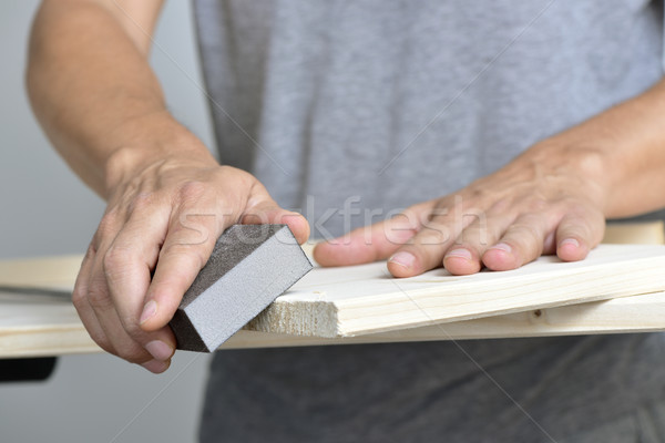 young man sanding a wooden board with a sanding block Stock photo © nito