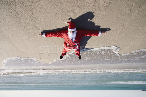 santa claus lying on the sand of a beach Stock photo © nito