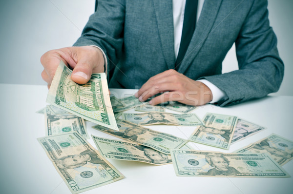 man in suit giving dollar bills Stock photo © nito