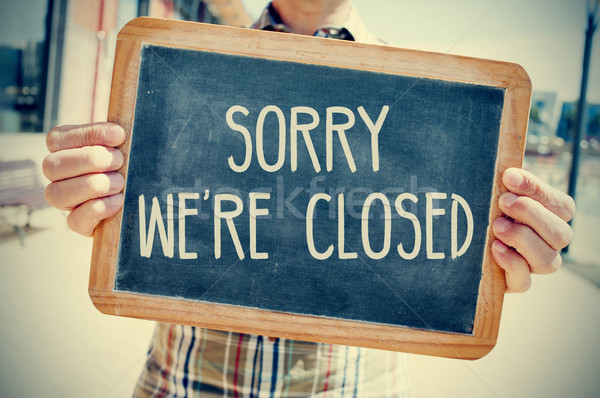 young man with a chalkboard with the text sorry we are closed, f Stock photo © nito