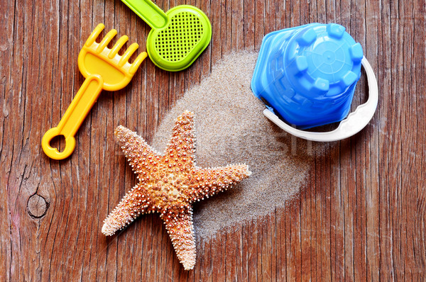 starfish, sand and beach toys on a rustic wooden surface Stock photo © nito