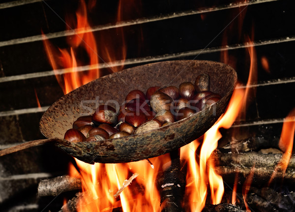chestnuts roasting in the flames of a log fire Stock photo © nito