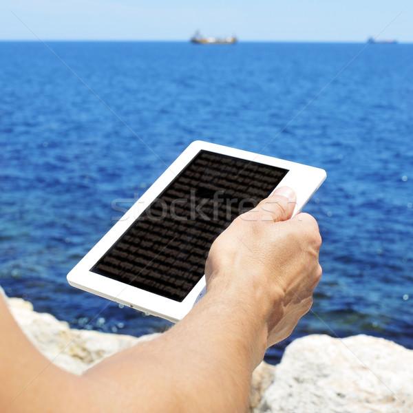 Młody człowiek czytania ebook morza książki technologii Zdjęcia stock © nito