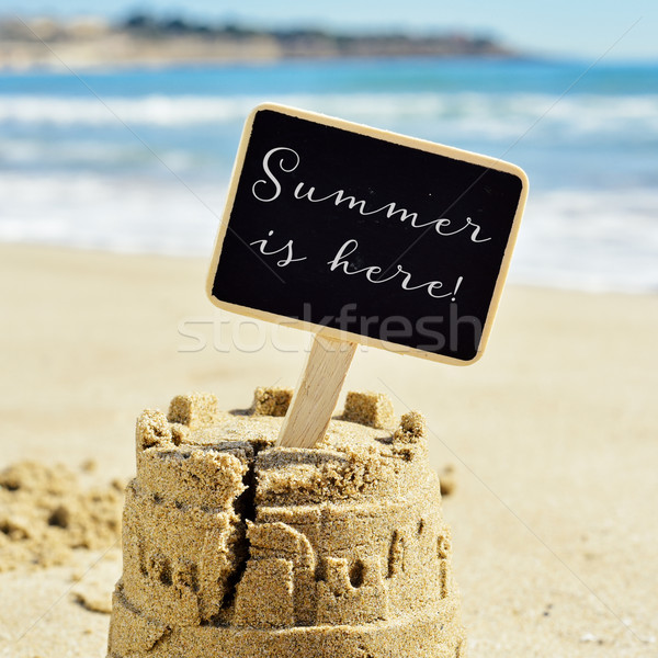 text summer is here in a signboard topping a sandcastle Stock photo © nito