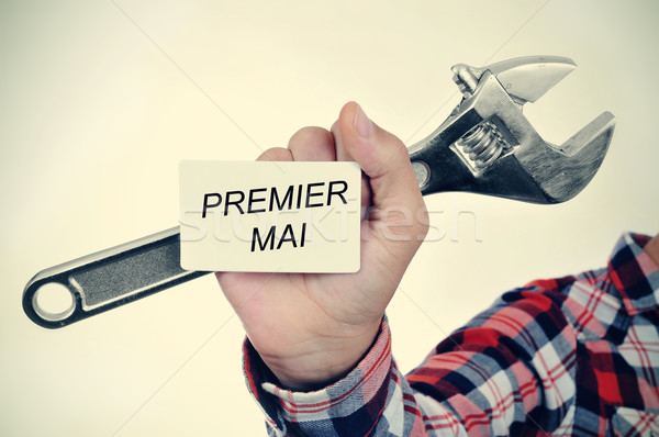 man with adjustable wrench and signboard with text premier mai,  Stock photo © nito