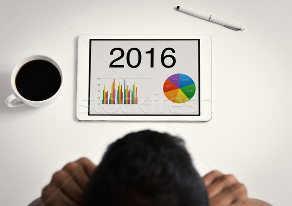 man observing charts of 2016 in his tablet Stock photo © nito