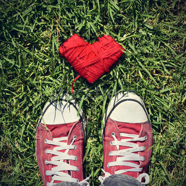 man feet and heart-shaped coil of red cord on the grass, vignett Stock photo © nito