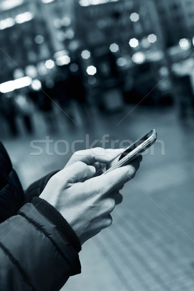 young man using his smartphone in the street at night Stock photo © nito