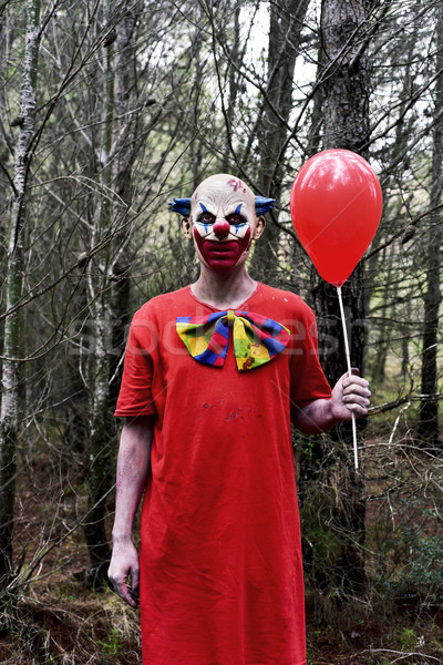 scary evil clown with a red balloon in the woods Stock photo © nito