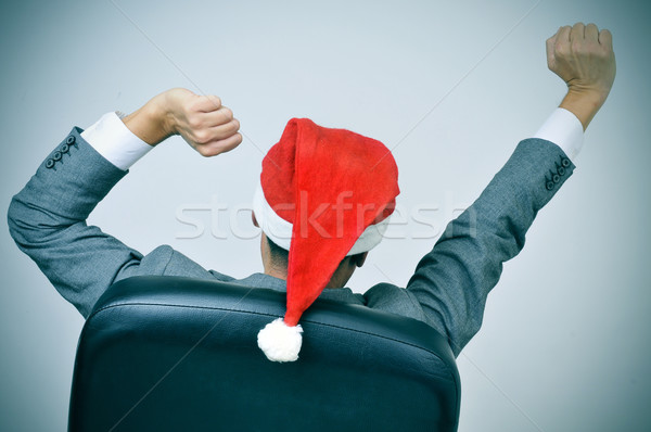 man with a santa hat stretching his arms in his office chair Stock photo © nito