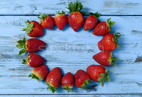 strawberries forming a circle on a blue wooden surface Stock photo © nito