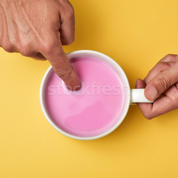 man soaking his finger in a pink milkshake Stock photo © nito