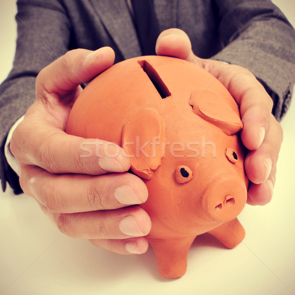 Stock photo: man in suit with a piggy bank