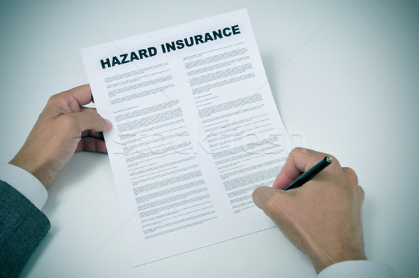 a young man signing a hazard insurance policy Stock photo © nito