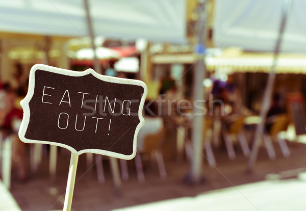 chalkboard with the text eating out in the terrace of a restaura Stock photo © nito