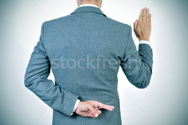 young man swearing an oath, crossing his fingers in his back Stock photo © nito