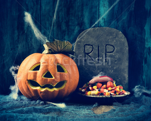 carved pumpkin, gravestone and Halloween candies Stock photo © nito