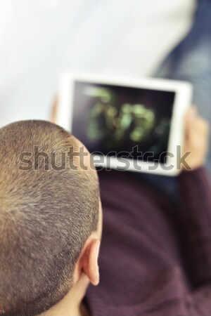 Stock photo: young man watching porn in his tablet
